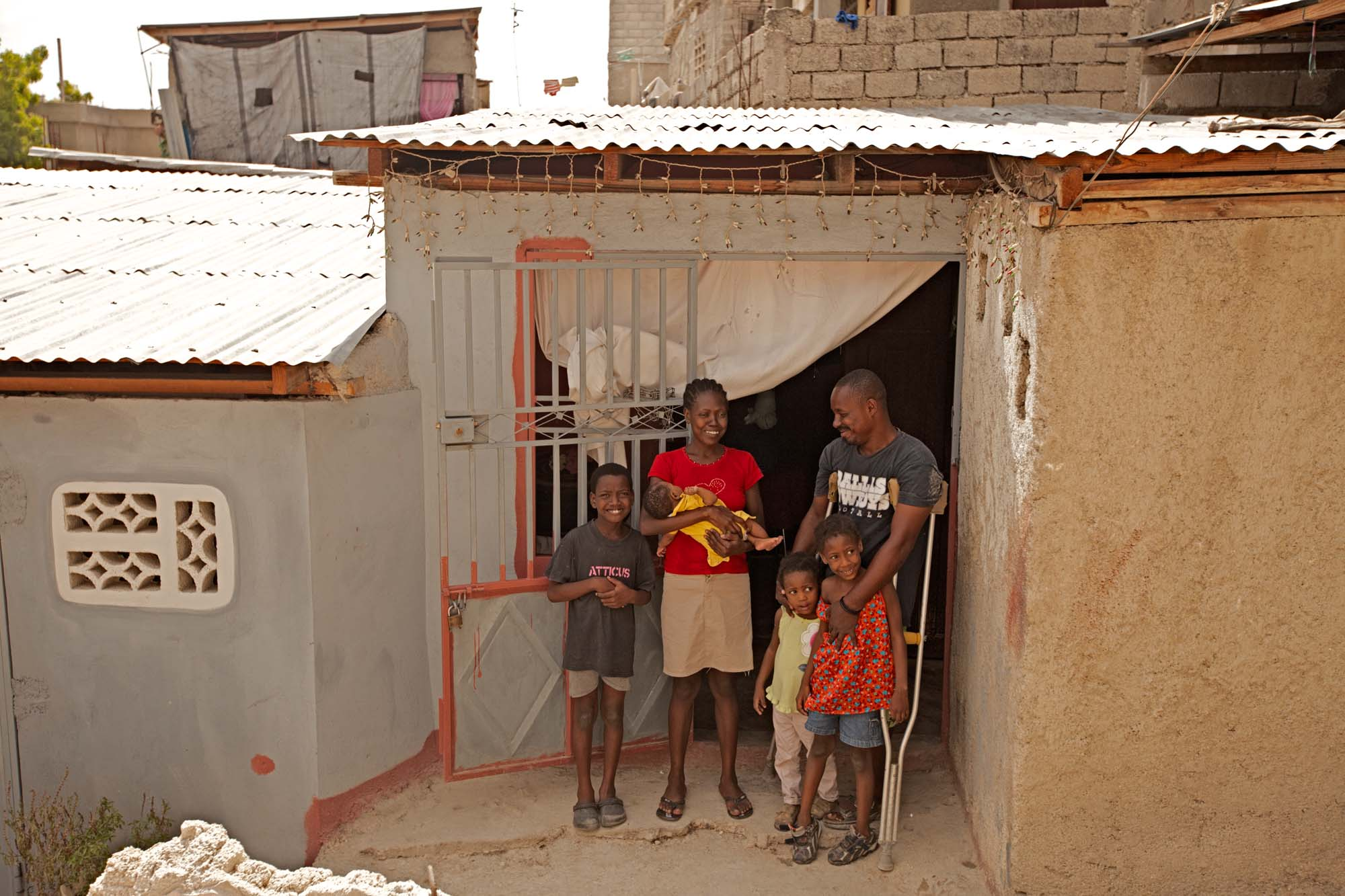 A family group stand in front of doorway of a small concrete house with a tin roof.
