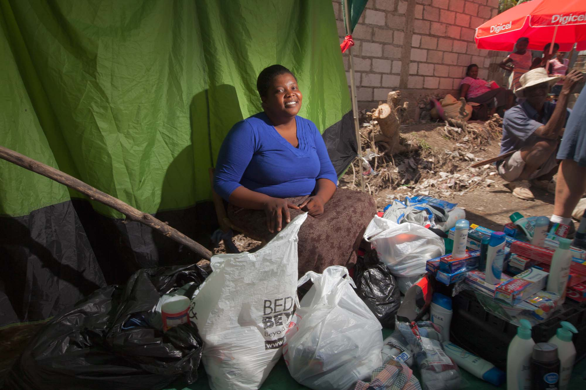 A smiling women sits surrounded by items for sale.