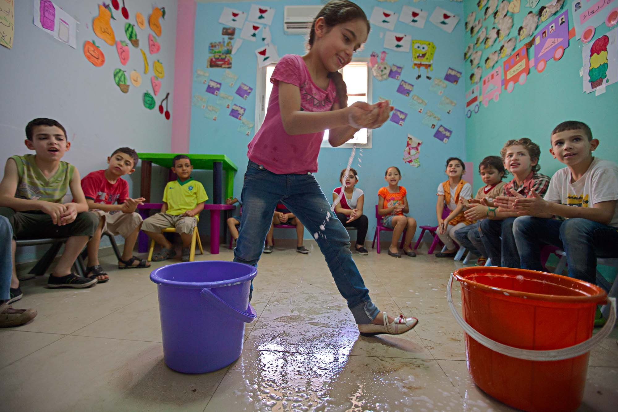 A smiling girl passes handfuls of water between two buckets surrounded by children sitting on chairs.