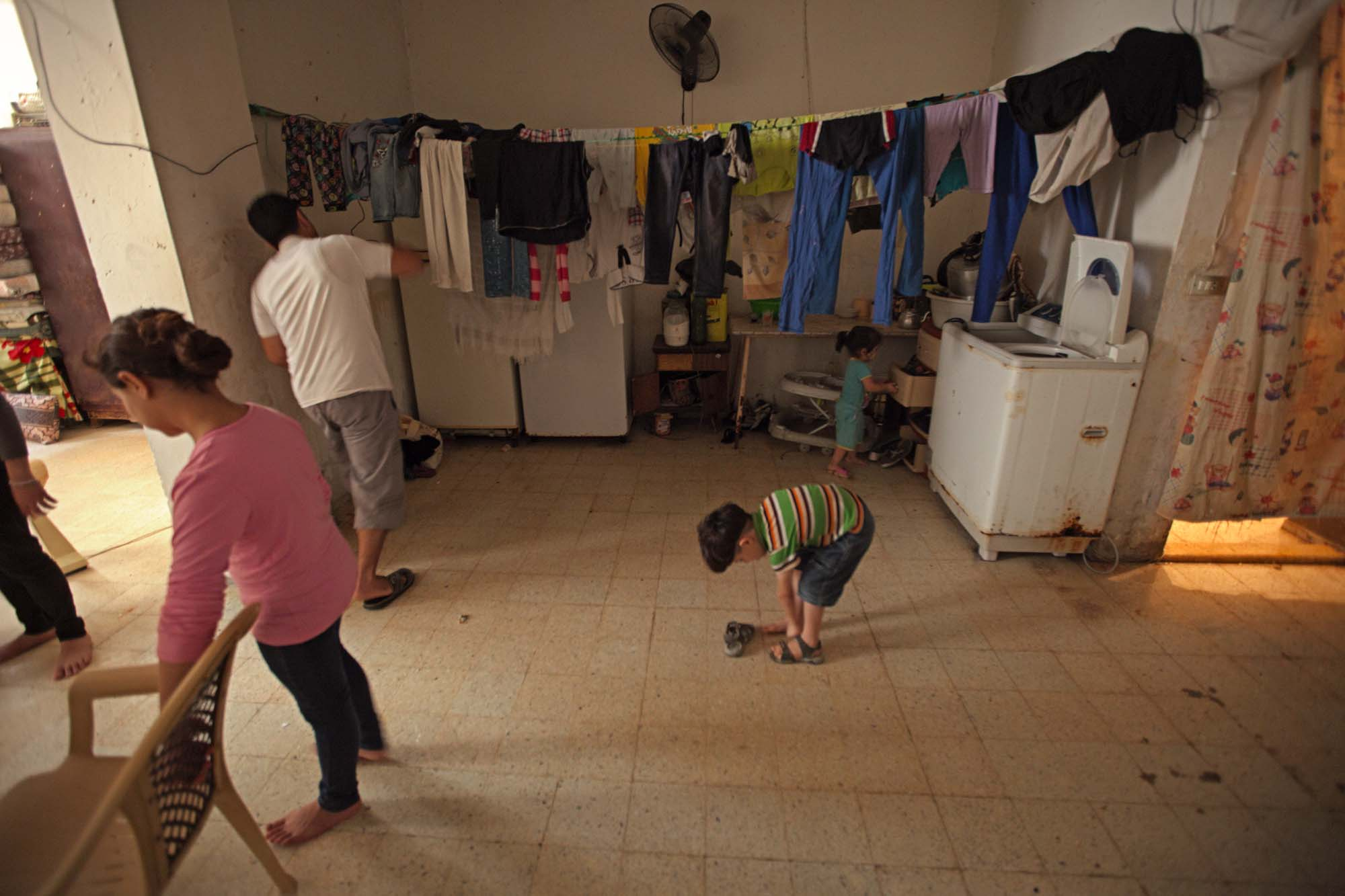 A family of people move around a room with a kitchen on one side and clothes hanging on a line.