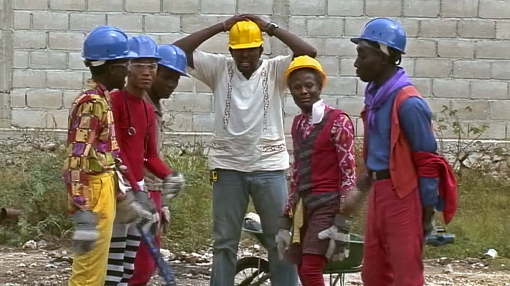 A film clip of a group of men wearing hard hats, dressed in unusual clothing standing in a building site.