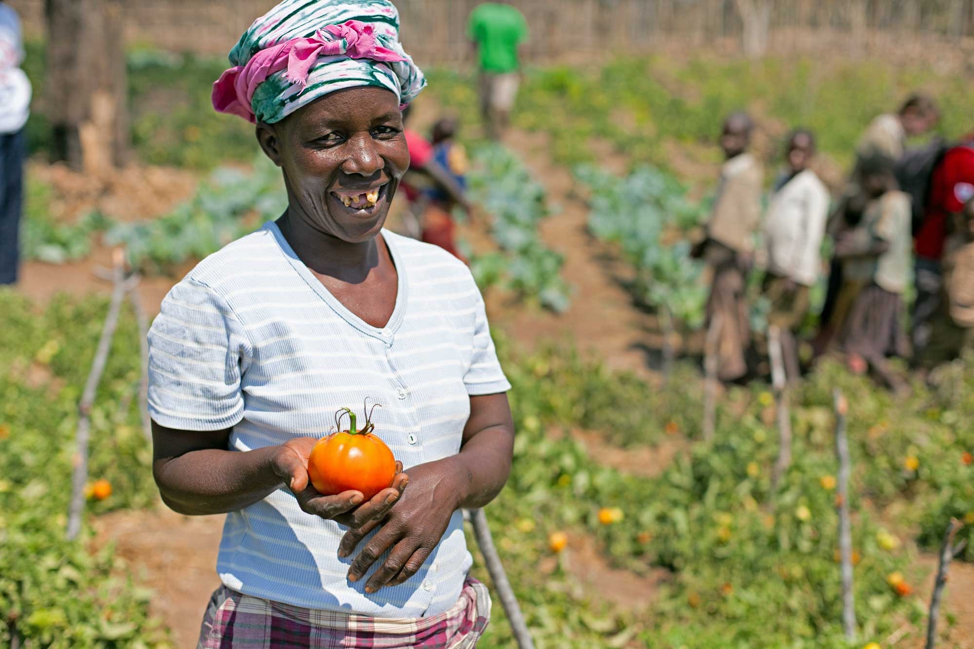 Tino Gente stands in her field smiling and holding a ripe tomato.