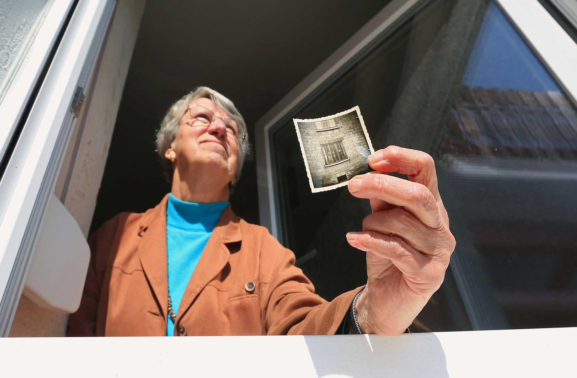Edith Foth holds a photograph standing at a window.