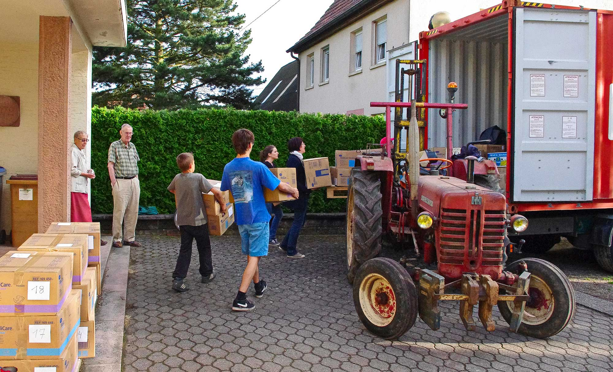 Agnes HIrschler and Jean Hege stand on the porch of a building watching a group of people load boxes into a container with a tractor in the foreground.