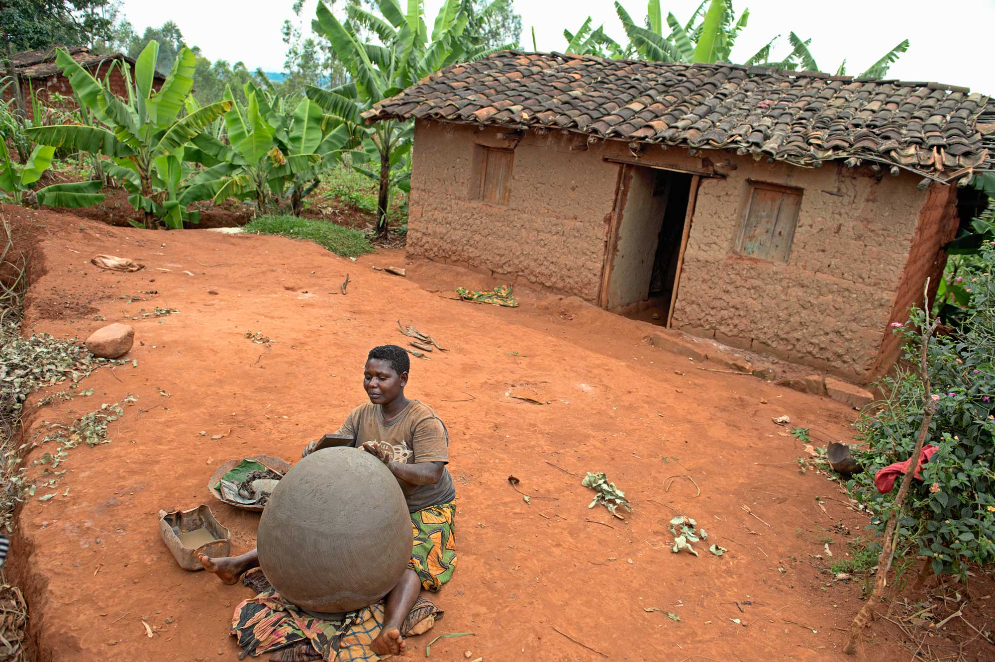 A women sits on the ground out side of a building shaping a large pot.