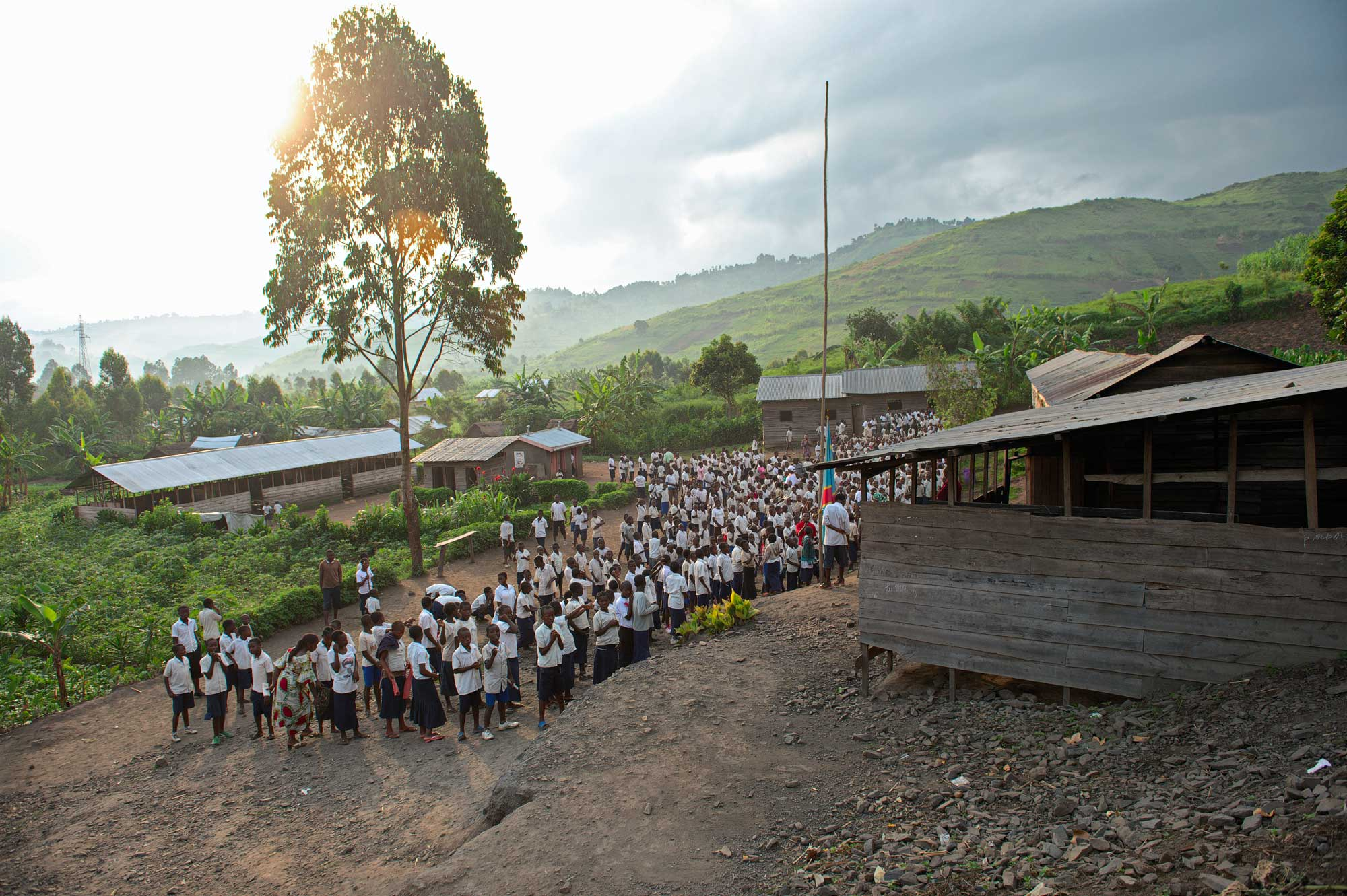 Children gather outside low wooden buildings in a valley.