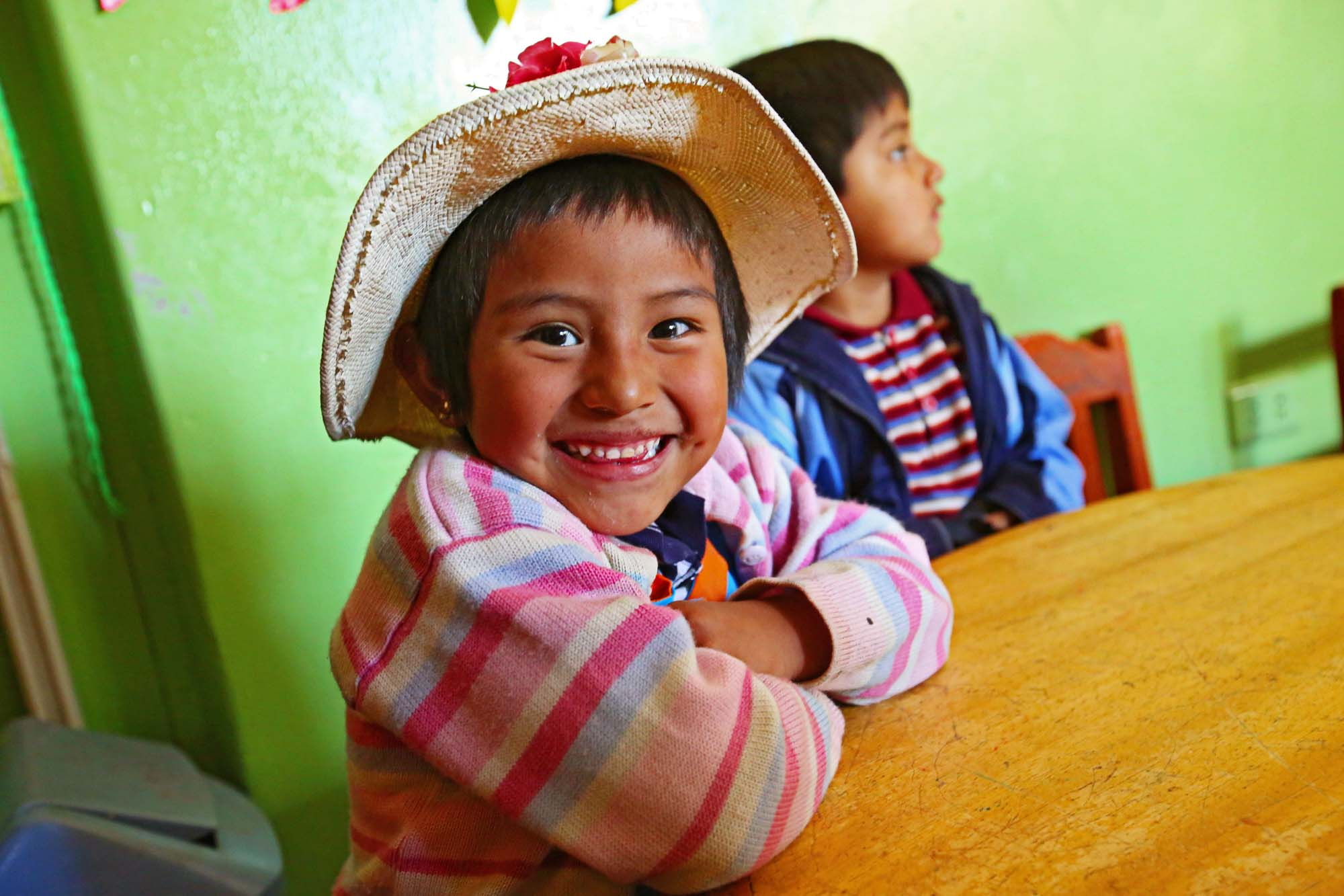 A young girl in a straw hat smiles