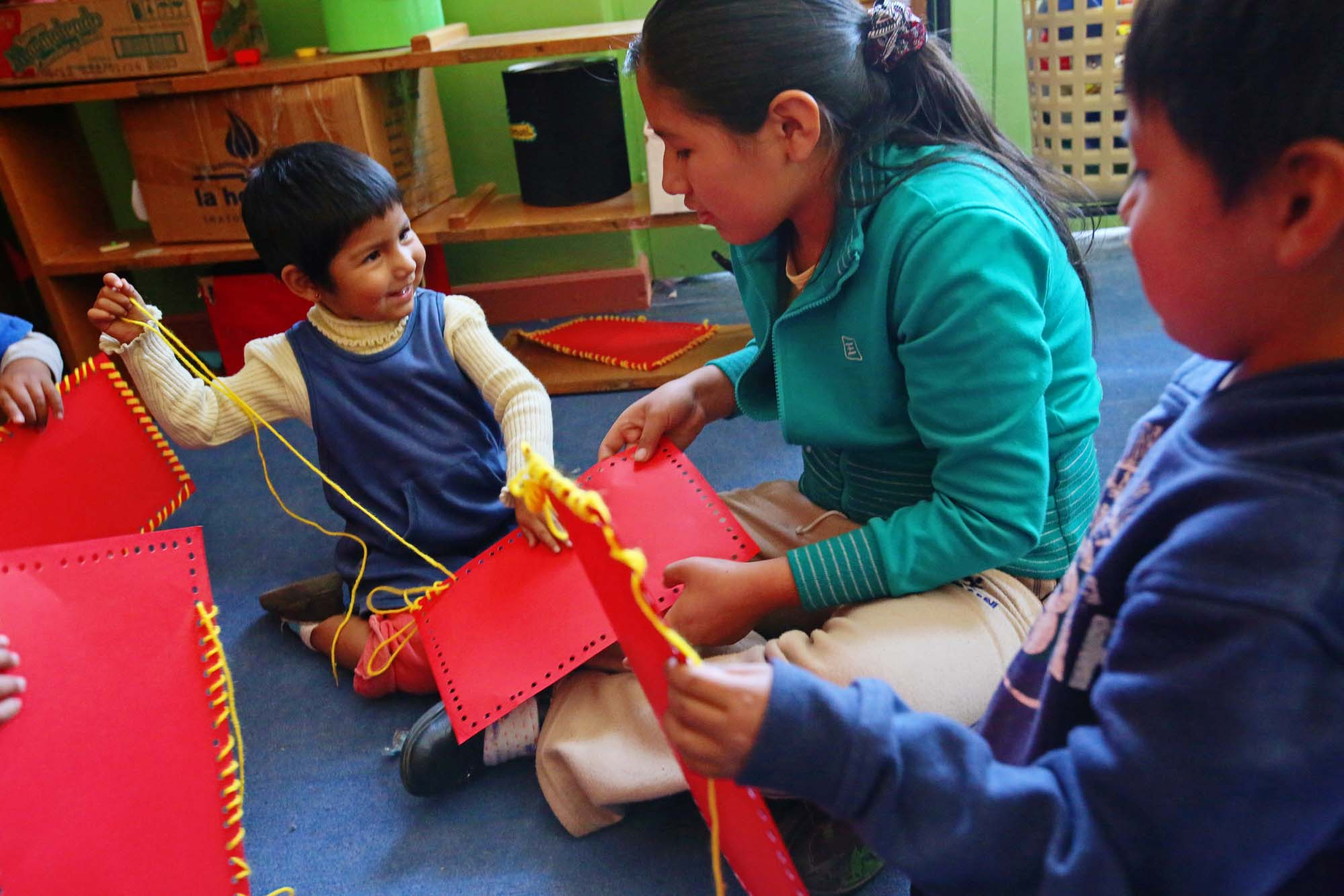 A smiling toddler threads fabric squares with an older student
