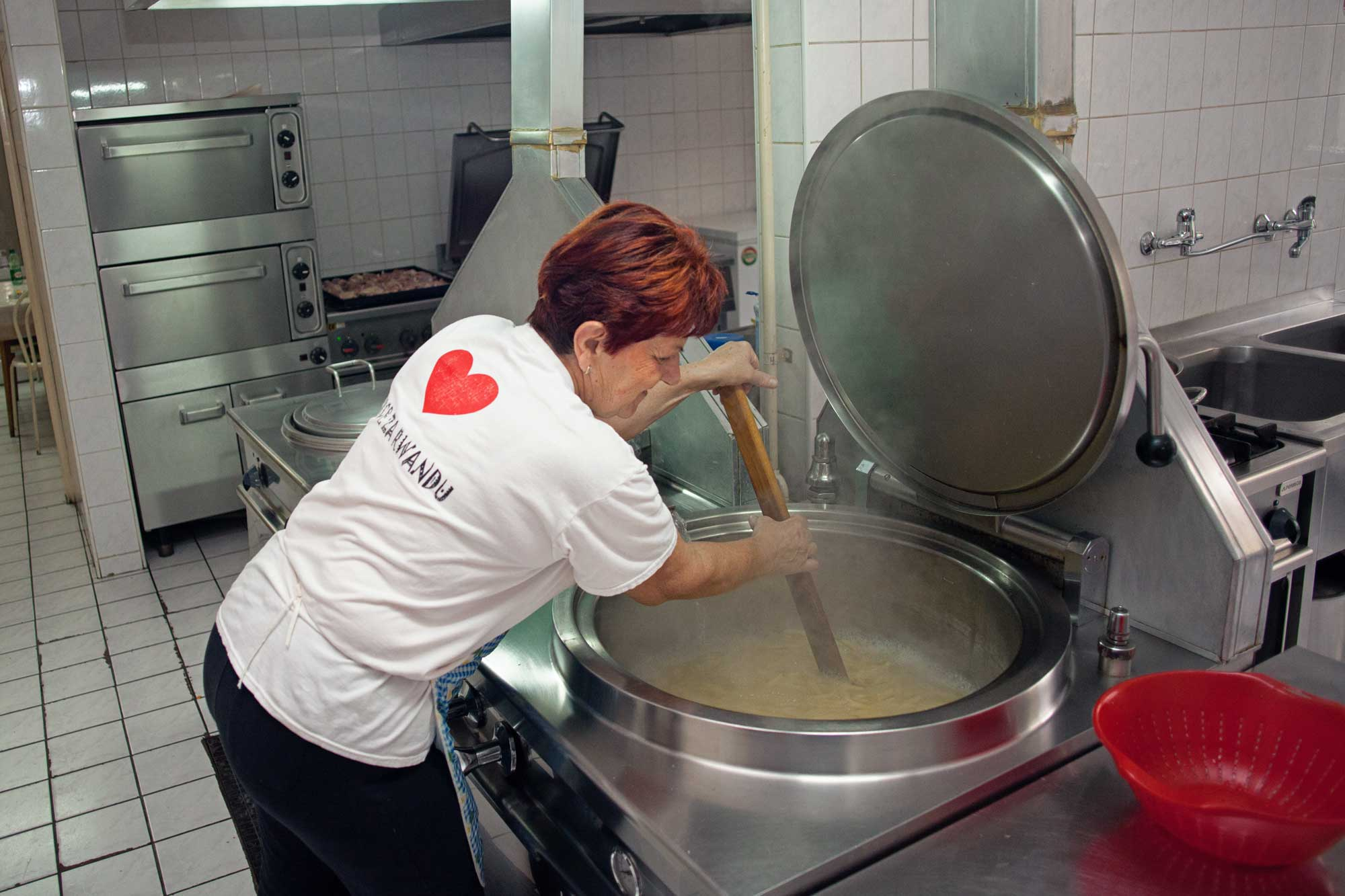 A volunteer stirs a huge pot of simmering sauce.