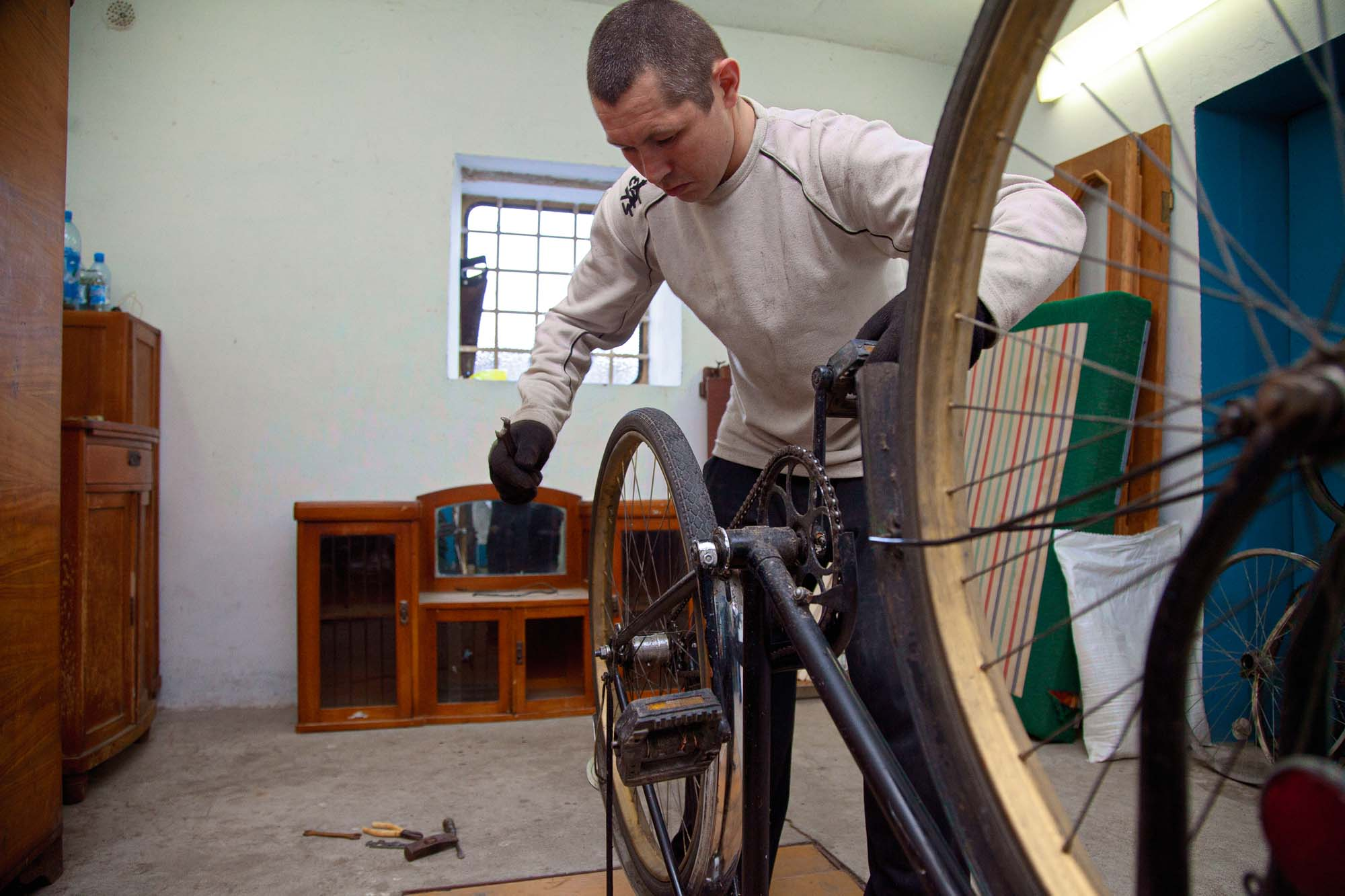 Vitalik Gorbunov leans over an upturned bicycle
