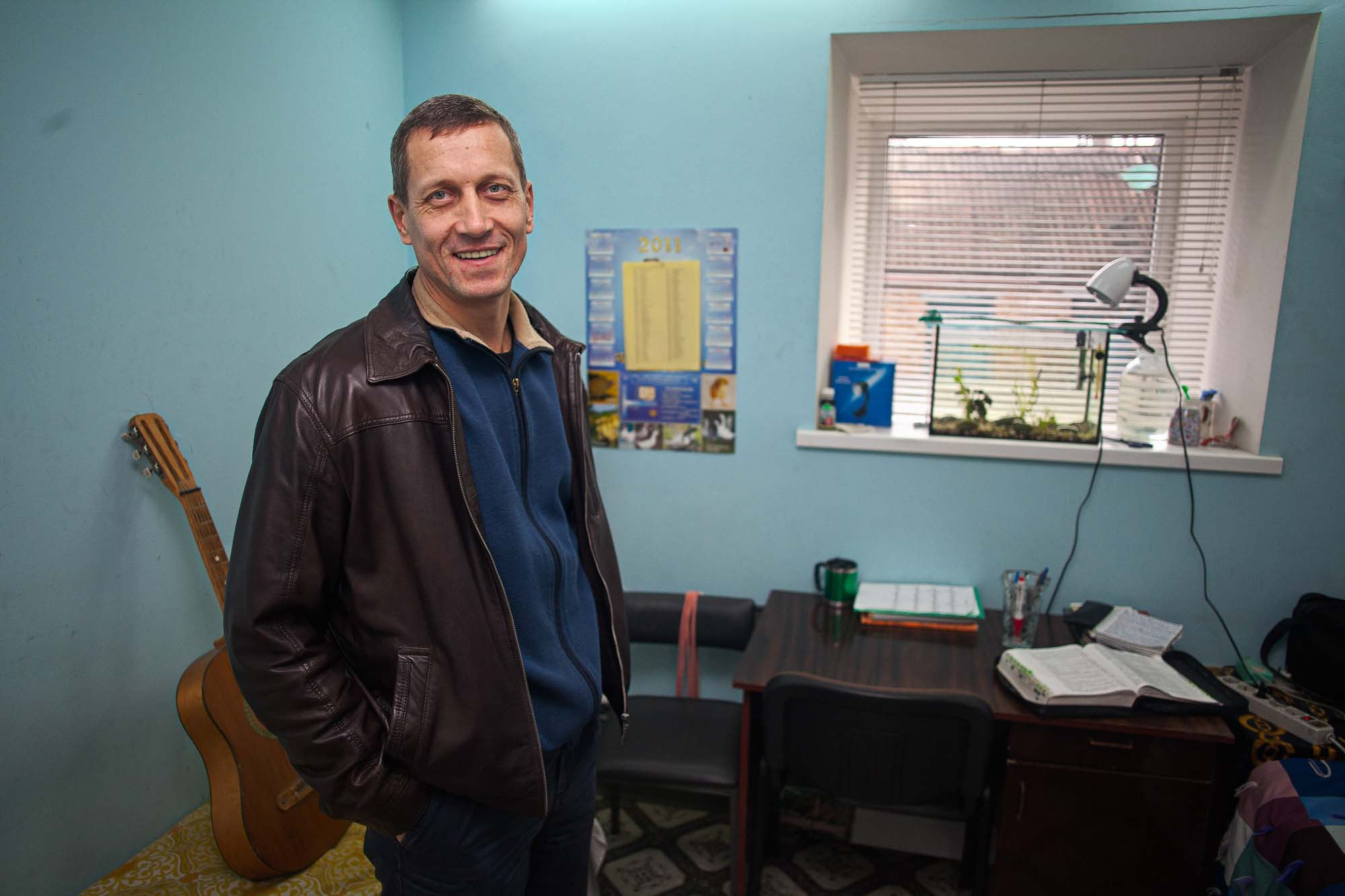 Slavik Lobatch smiles, standing in a room with desk