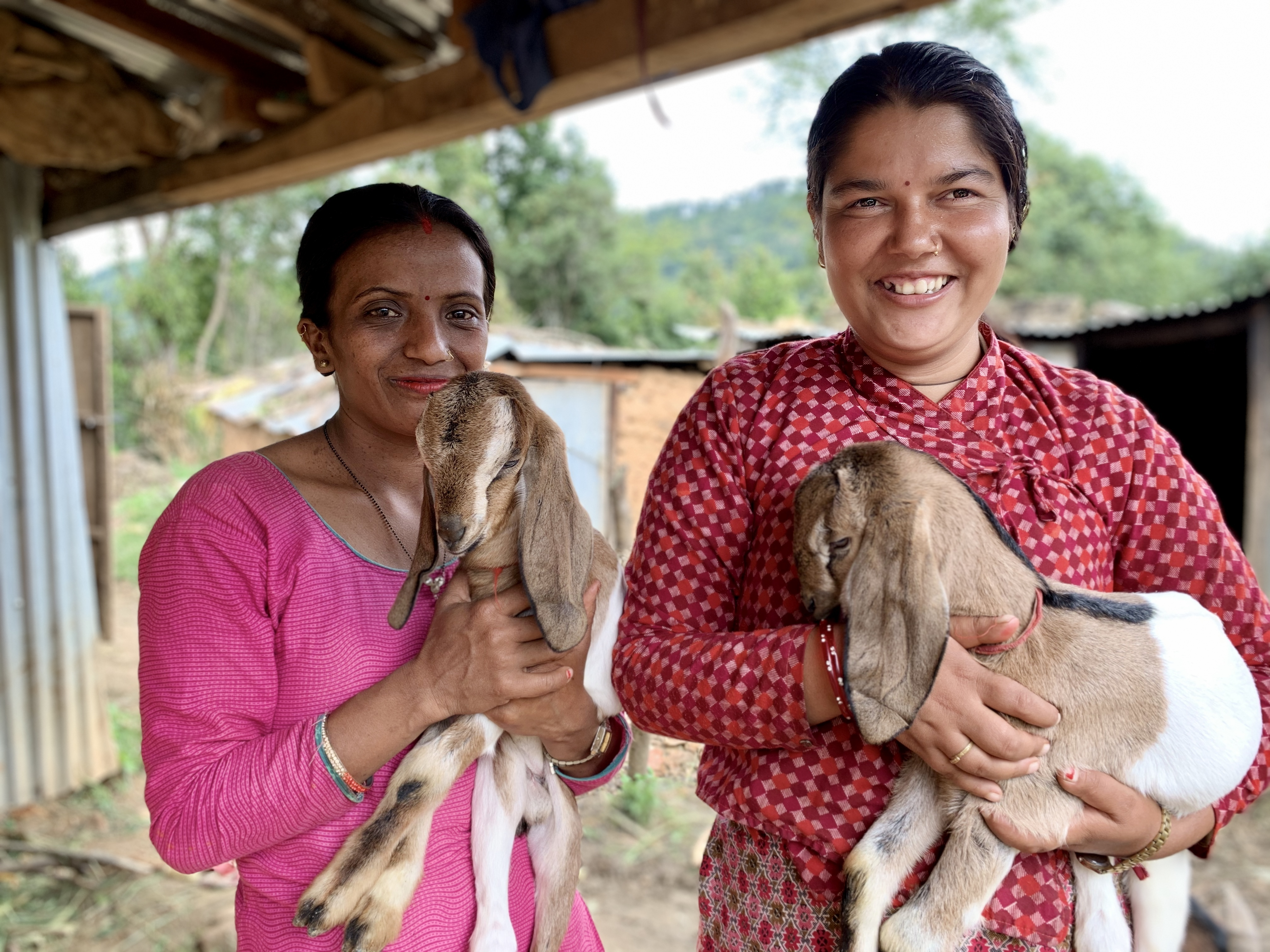 Kamala Sapkota (right), with her sister Pompa Humagaim, at her home in the hills of Kavrepalanchok, Nepal. With your support, Kamala graduated from  a mental health program. They are holding baby goats that Kamala was given through the project which allow her to earn income and live independently. (MCC photo/ Paul Shetler Fast)