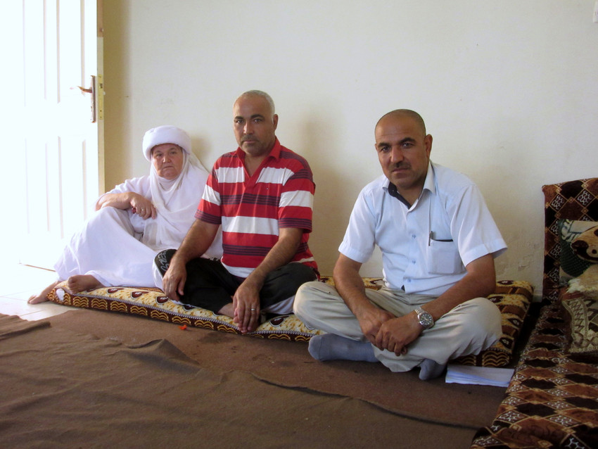 Qasim, right, with his brother Haji, centre, and mother Huda, left, in the living area of the new apartment they rent using assistance from REACH.