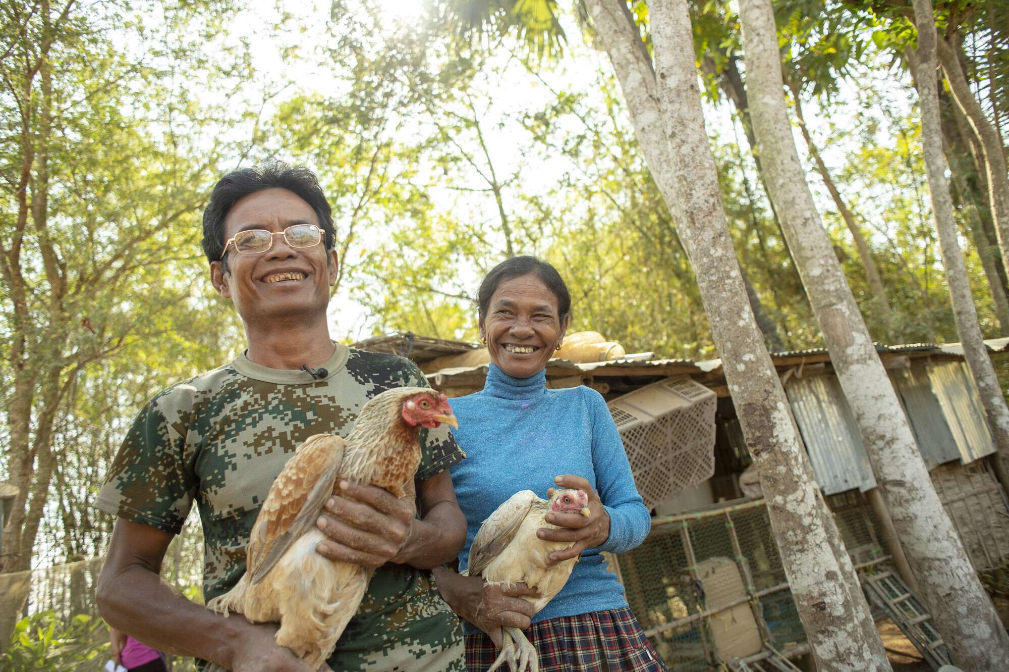 Chim Yean and Reach Koeun with chickens at their farm in the village of Prey Toum, Cambodia. Your support has allowed them to purchase the tools, seeds and other necessities to build a thriving farm. (MCC photo/ Matthew Lester)