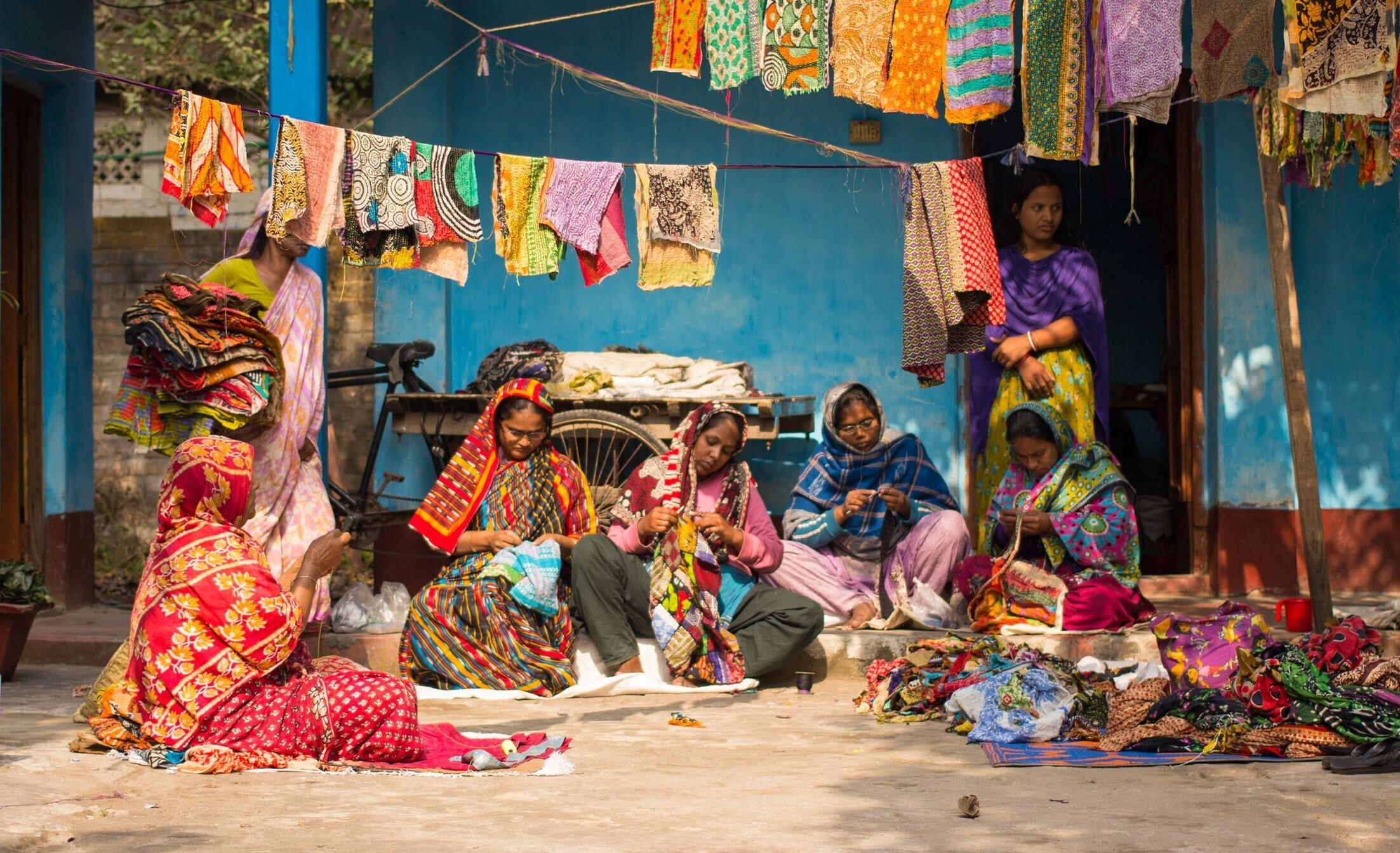 A group of artisans from the Hajiganj Handicrafts crochet unit sit outside their workshop stitching blankets from recycled saris in 2018. These artisans sold many blankets through Ten Thousand Villages.  (Photo courtesy of  Ten Thousand Villages)