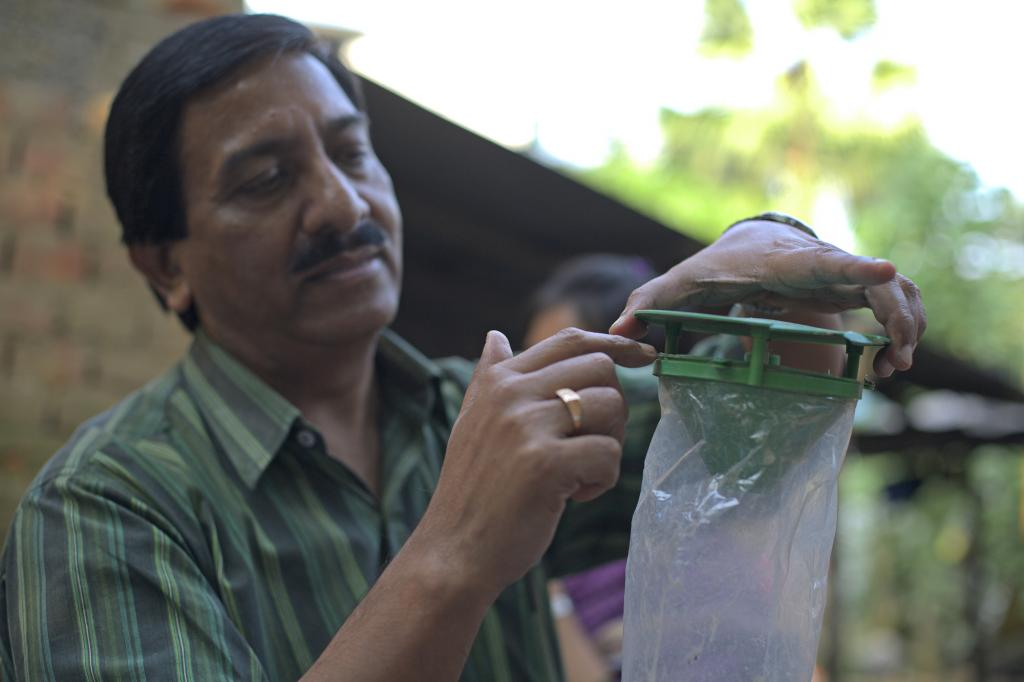 """<span class=""""photo-caption"""">Using sustainable and organic methods to combat pests and fertilize soil gives farmers an alternative to purchasing pesticides and fertilizers each growing season. MCC project officer Achinta Das shows an insect trap supplied by ABSK.</span><span class=""""photo-credit"""">Melissa Hess</span>"""