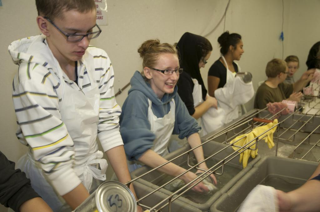 """<span class=""""photo-caption"""">Step 7: The freshly cooked and cooled cans are individually hand-washed and dried off by volunteers.</span><span class=""""photo-credit"""">MCC photo by Anthony J. Siemens</span>"""