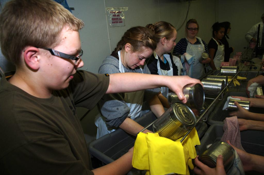 """<span class=""""photo-caption"""">Washing the cans is important to remove any baked on meat residue and so that the label can be applied.</span><span class=""""photo-credit"""">MCC photo by Anthony J. Siemens</span>"""