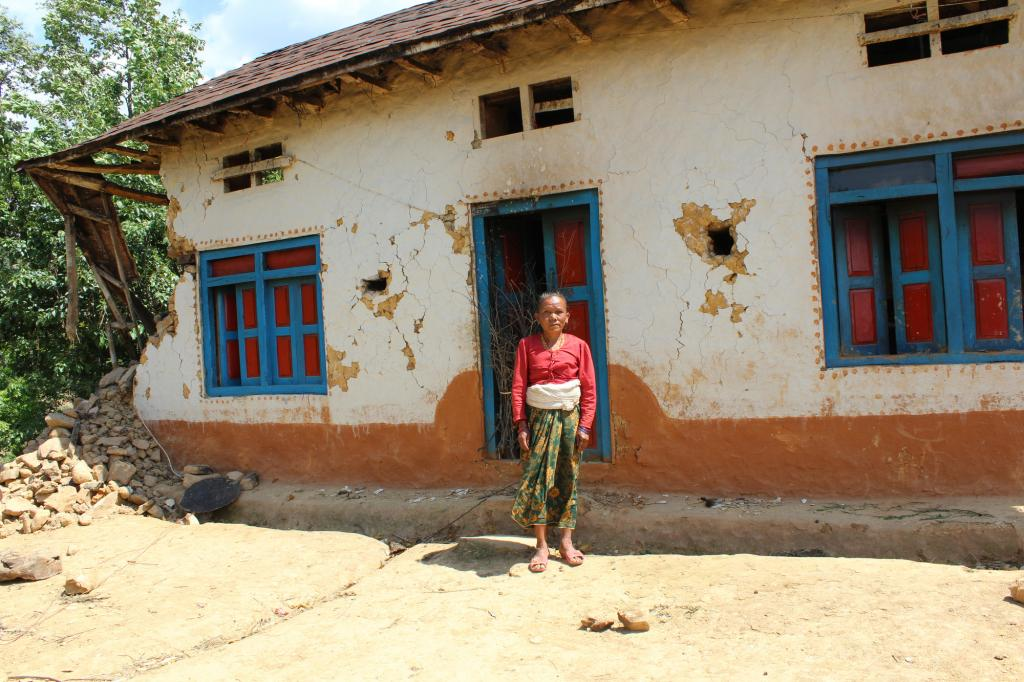 "<span class=""photo-caption"">Anita Lama, 71, standing in front of her damaged house in Lalitpur, Nepal. Lama's family had two houses in their yard and now both are unlivable. They have been living under tarps since the earthquake occurred. </span><span class=""photo-credit"">MCC photo/Binod Deshar</span>"