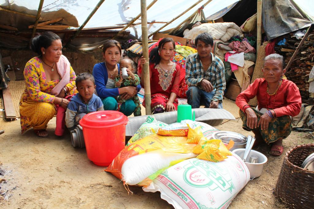 "<span class=""photo-caption"">Lama (right) and her family with their relief materials from MCC, distributed through our Nepalese partner the Rural Institution of Community Development (RIOCD). Before they received sleeping mats from MCC they were sleeping on a plastic sheet on the ground. They were only able to retrieve a small amount of their stored rice and other food from their kitchen. MCC also provided the family with three weeks of food (rice, lentils and oil). </span><span class=""photo-credit"">MCC photo/Binod Deshar</span>"