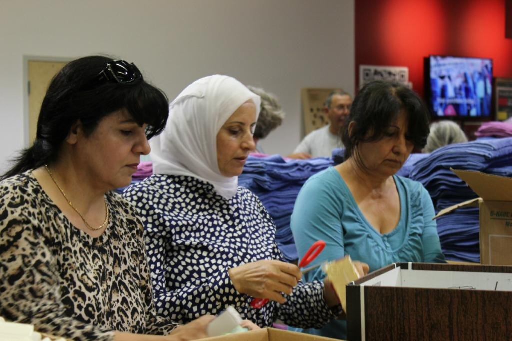 """<span class=""""photo-caption"""">Members of Shamrose, a local Syrian group, joined MCC Ontario to help pack relief and hygiene kits to be sent to their home country.</span><span class=""""photo-credit"""">MCC Photo/Josh Hissa</span>"""