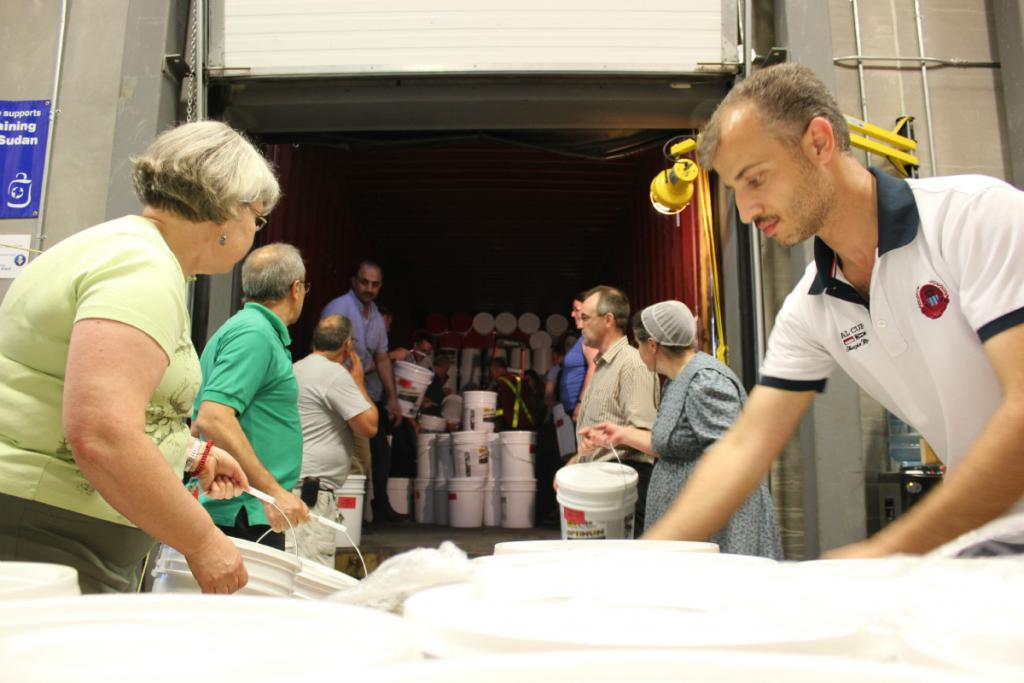 """<span class=""""photo-caption"""">Volunteers from the local Syrian and Mennonite communities help pack a cargo container with more than 1,000 relief and hygiene kits.</span><span class=""""photo-credit"""">MCC Photo/Josh Hissa</span>"""