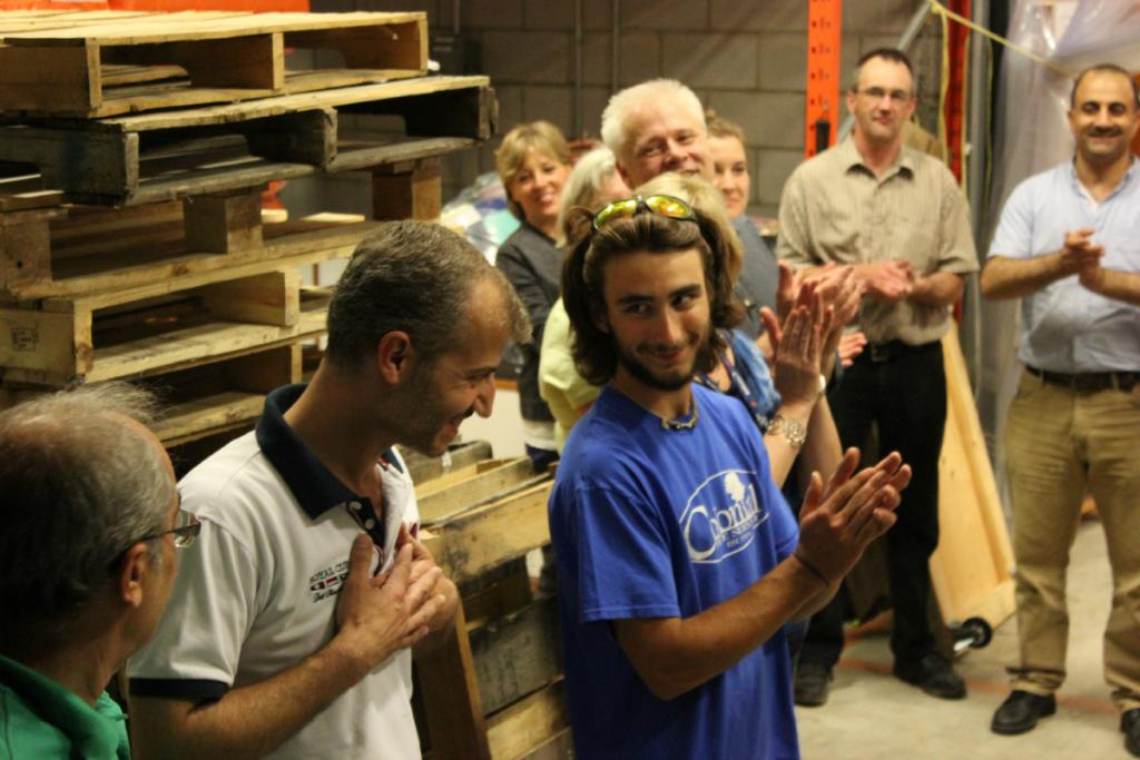 """<span class=""""photo-caption"""">Mohammed, a refugee from Syria who arrived in Canada only two weeks before this photo was taken, is welcomed by volunteers gathered to pack up and bless a cargo container holding over 1,000 relief and hygiene kits bound for Syria.</span><span class=""""photo-credit"""">MCC Photo/Josh Hissa</span>"""