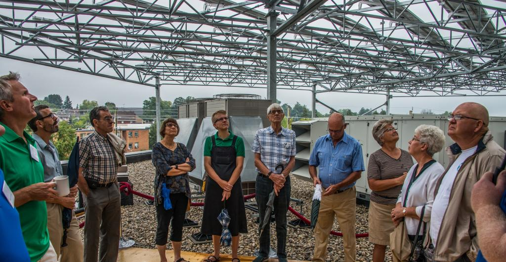 """<span class=""""photo-caption"""">Guests tour the rooftop at 50 Kent featuring the 774 recently installed solar panels.</span><span class=""""photo-credit"""">Community Energy Development Co-op/Al Doerksen</span>"""