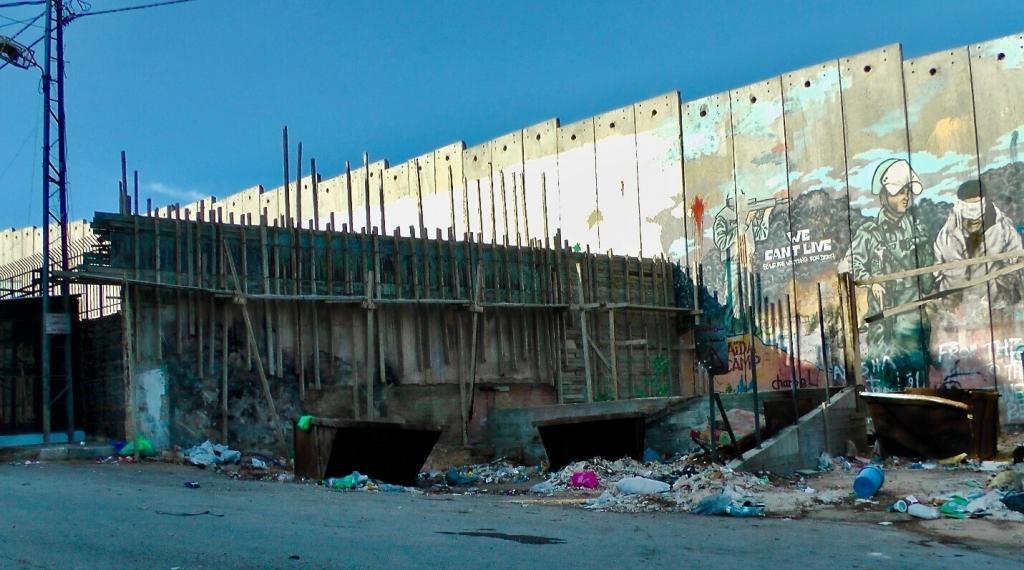 "<span class=""photo-caption"">Graffiti covers the wall encasing the AidaRefugee Camp.</span><span class=""photo-credit"">Photo/Betty Enns</span>"