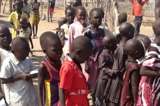 Children wait in line for a food distribution