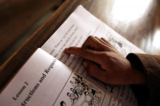 A boy follows along in his textbook during English class at the Baromari Mission school in Bangladesh.