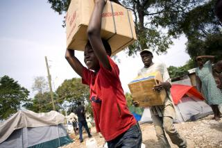 Nicholas Mardoche carries a case of canned meat from a delivery truck to a storehouse in the camp where he lives.