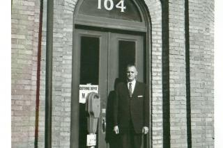 J.M. Klassen, MCC Canada's first executive director, stands in front of the Canadian Mennonite Relief and Immigration Council which merged with other Mennonite agencies to become MCC Canada. This building became the first office of MCC Canada.