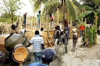 Haitian workers build a new reservoir to hold water from one of the three mountain springs that provides water to the town of Desarmes. Water from the reservoir will flow into pipes that will deliver reliable, drinkable water to households and public kiosks in the area.