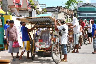 MCC is supplying building materials, including plywood and tin sheets similar to those being loaded onto this bicycle-powered rickshaw, to almost 3,000 Filipino families whose homes were destroyed by Typhoon Haiyan. In addition, MCC is paying local people to build the houses in the towns of Naval and Dulag.