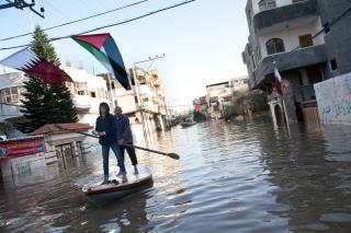 A week after torrential rains caused floodwaters to reach about 3.6 meters, Palestinians use fishing boats to assist residents in retrieving belongings from homes along flooded streets in the Al Nafaq section of Gaza City, Dec. 18.