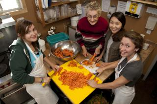 Volunteers, Sasha Homenko, Anna Marie Giesbrecht, Laeun Kin and Birte Wiebe (left to right) get to know each other as they work in the kitchen at Sam's Place.