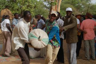 Two men carry a bag of millet at an MCC-supported food distribution in south-west Niger. Names are withheld for security reasons.