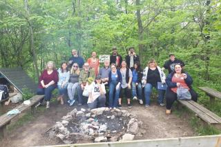 Group of people laughing together in a forest in front of campfire.