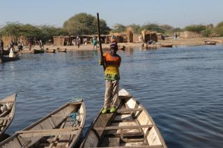 A young child stands on a fishing boat in Lake Chad