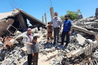 Family stands amoung the rubble of destroyed building.