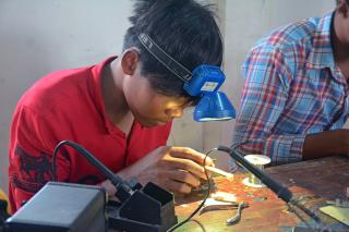 Student wearing a headlamp working in electronics repair class