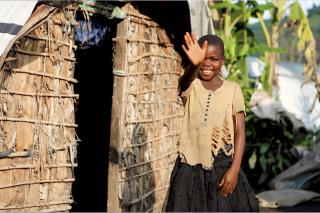 A child stands in front of a hut and waves at the camera