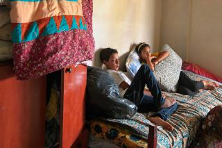 A teenage boy and girl sit on a bed with a quilt hanging on the cupboard next to them