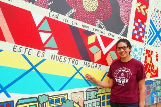"Woman standing by mural wall with Spanish writing that reads ""This is my home""."