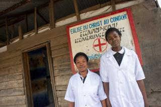 Two nurses stand in front of hospital