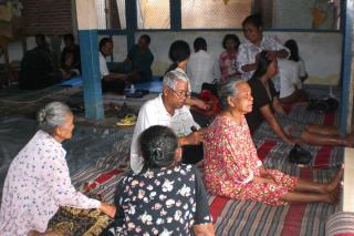 Yonathan Ibnu Budiyanto applies acupressure to the back of a woman.