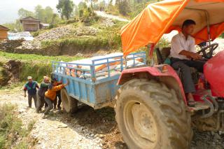 A tractor pulls a wagon full of relief supplies up a gravel hill in the Okhaldhunga District of Nepal.