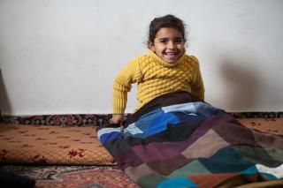 Reem sits with an MCC comforter her family received
