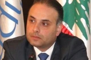 A man wearing a black suit and blue tie sits in front of two flags.